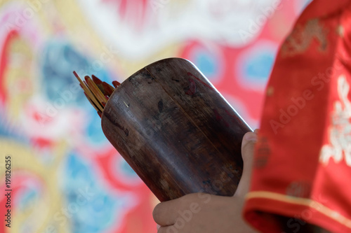 Photo  Happy Chinese New Year 2018, Asian Girl Shaking Fortune Stick in Bamboo Box use for Predict future