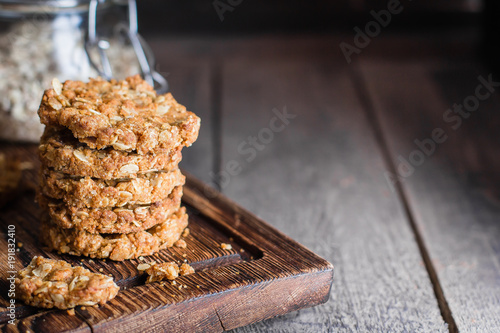 Homemade oatmeal cookies on wooden board on old table background Fototapete