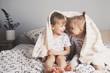 Leinwandbild Motiv Two pretty kids embrace under blanket