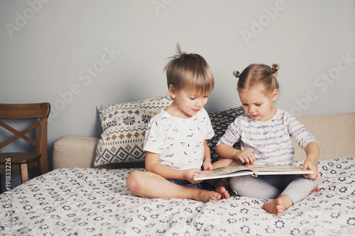 Photo  Two kids sitting on bed and reading a book