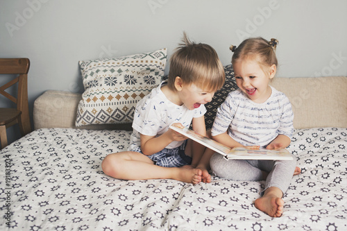 Two kids sitting on bed and reading a book Fototapet