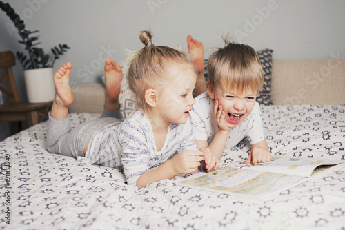Two kids sitting on bed and reading a book Wallpaper Mural