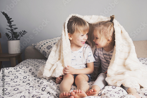 Two pretty kids embrace under blanket