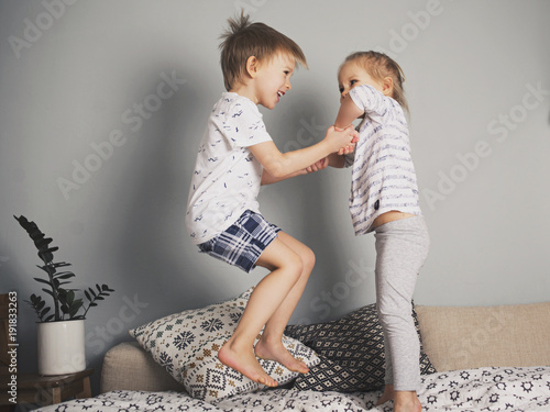 Pretty kids jumping on the bed together Tablou Canvas
