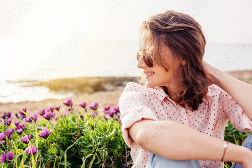 Beautiful young curly stylish girl in a pink shirt on the beach, summer and spring portrait, joy and nature