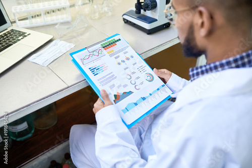 Over shoulder portrait of young Middle-Eastern scientist looking at data charts while working on medical research in laboratory
