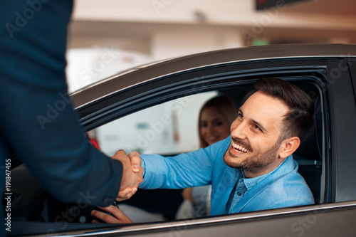 Fotografía  Young couple shaking hands after a successful car buying