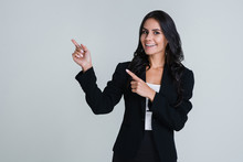 Look Here! Beautiful Young Businesswoman Pointing Away And Looking At Camera With Smile While Standing Against White Background