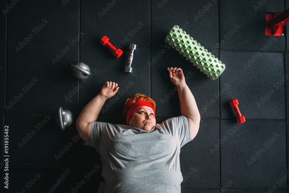 Fototapeta Tired fat woman lies on the floor in gym