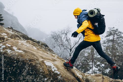 Papiers peints Glisse hiver Man in yellow jacket climbs the rocks in the winter mountains
