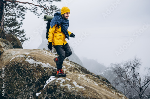 Stickers pour portes Glisse hiver Man in yellow jacket climbs the rocks in the winter mountains