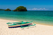 fishboat on sand and two small islands on tropic turquoise sea and blue sky.
