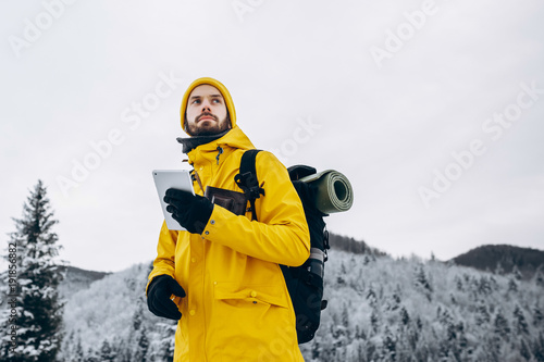 Poster Glisse hiver Man in yellow hiking suit walks with a tablet in his arms over winter mountains covered with snow