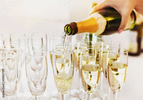 Pouring champagne into wine glasses. Champagne flutes on a wedding party