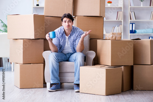 Obraz Young man moving in to new house with boxes - fototapety do salonu