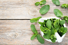 Fresh Mint Leafs In Mortar On Grey Wooden Table