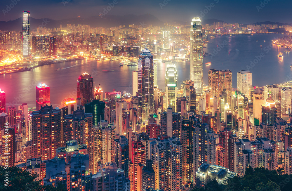 Fototapeta Scenic view over Hong Kong island, China, by night. Multicolored nighttime skyline with illuminated skyscrapers seen from Victoria Peak