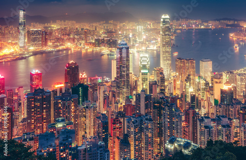 Fotobehang Aziatische Plekken Scenic view over Hong Kong island, China, by night. Multicolored nighttime skyline with illuminated skyscrapers seen from Victoria Peak