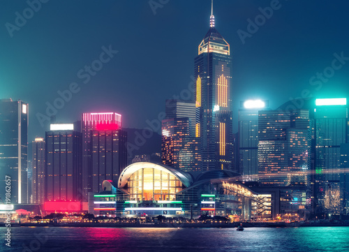 Scenic skyline of Hong Kong island with skyscrapers. Victoria harbor at night. Colourful travel background.