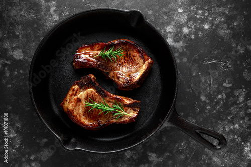 Valokuva  Cooked Pork Loin chops in rustic skillet, pan with rosemary