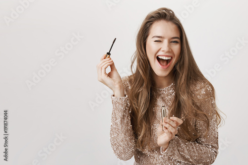 Valokuva  Indoor shot of positive attractive caucasian woman winking and smiling broadly while holding mascara and applying it, standing in evening dress over gray background