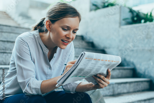 Content Lady Reading Newspaper on Stairs