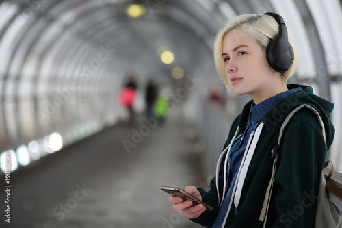 Fotografia  Young girl listens to music in big headphones in the subway
