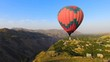 Aerial view of beautiful hot air balloon flying over mountain village, Armenia