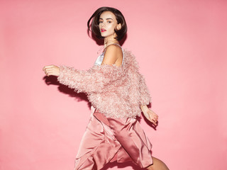 young fashion woman in pink clothes run on pink background