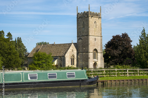 Canvas Late spring sunshine on colourful narrowboats moored near St Marys Church on the
