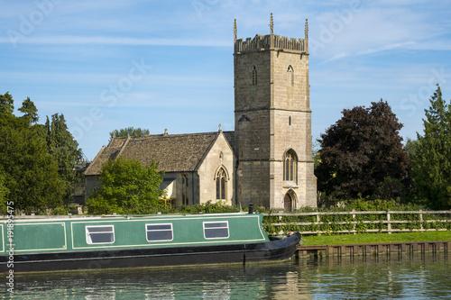 Tela Late spring sunshine on colourful narrowboats moored near St Marys Church on the