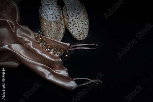 Fotografie, Obraz  pantofle,halka, korale na czarnym tle
