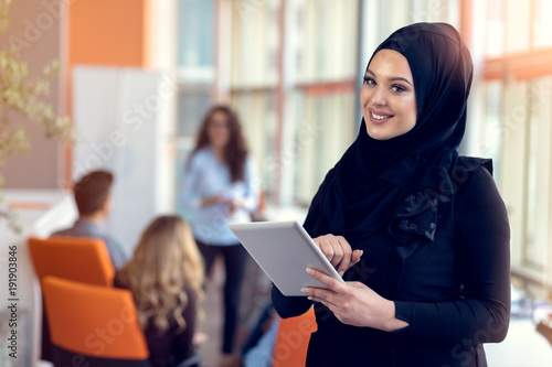 Pretty woman wearing hijab in front of laptop search and doing office work, business, finance and workstation concept Billede på lærred