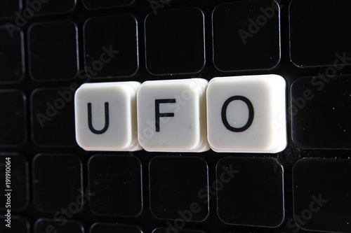 UFO text word title caption label cover backdrop background. Alphabet letter toy blocks on black reflective background. White alphabetical letters. White educational toy block with words