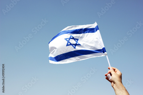Man holding Israeli flag against the wind celebrating independence day