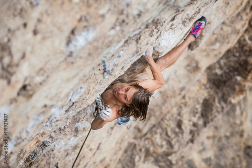 Fotomural shirtless male climber working hard to lead up a rock wall