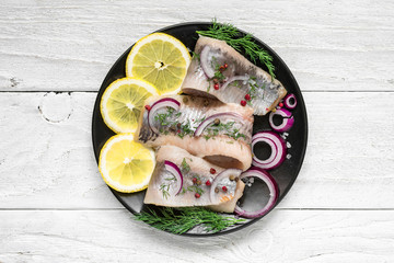 Fototapeta Herring fillet with salt, pepper, herbs, onion and lemon on black plate on white background