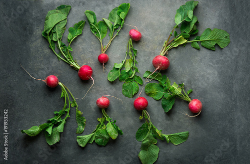 Fresh Raw Ripe Red Radishes with Green Leaves Scattered on Dark Concrete Stone Background. Top View Flat Lay. Minimalist Style. Creative Image Template for Website Banner.