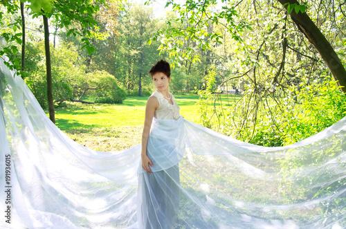 Fotografia  Oriental woman in long white dress Sunny afternoon strolls in the Park
