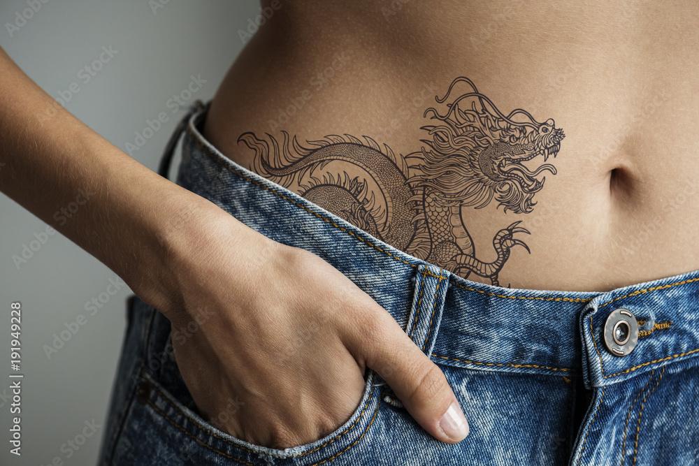 Fototapeta Closeup of lower hip tattoo of a woman