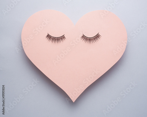 Wake up / Creative concept photo of heart with eye lashes on grey background.