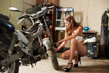Obraz na płótnie Canvas Searing brunette in short shorts and high-heeled sits near a motorcycle in the garage. The girl touches the front wheel