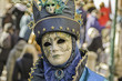 Portrait of a beautiful woman dressed as a blue wizard during the Venetian carnival party in San Marco square