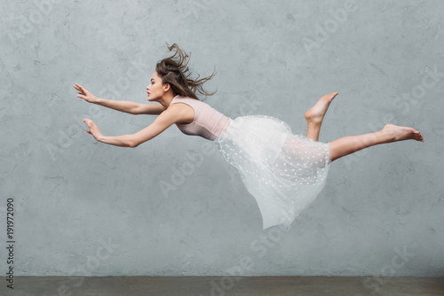 Obraz beautiful young woman in dress levitating and looking away on grey - fototapety do salonu