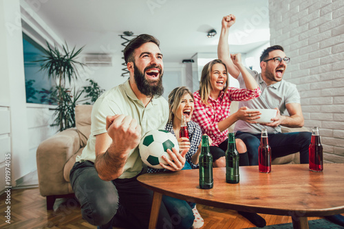 Fototapeta Happy friends or football fans watching soccer on tv and celebrating victory at home.Friendship, sports and entertainment concept. obraz