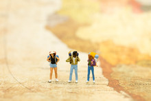 Miniature People: Travelers With Backpack Standing On World Map, Walking To Destination. Image Use For Travel Business Concept.
