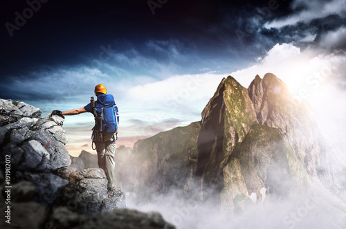 Mountain climber with stormy view over mountains