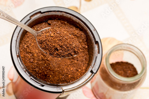 Wall Murals Chocolate coffee, ground in a coffee grinder, be filled upinto a jar with a spoon