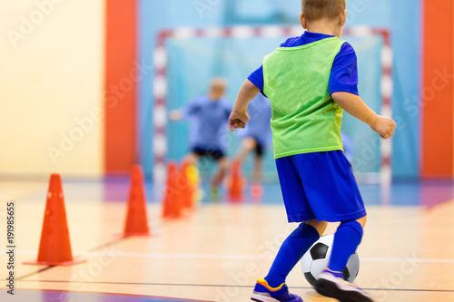 Soccer training dribbling cone drill. Football futsal training for children. Indoor soccer young player with a soccer ball in a sports hall. Player in blue uniform. Sport background.