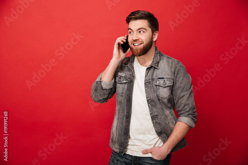 Image of young brunette man having call and talking on smartphone with pleasure, Canvas Print